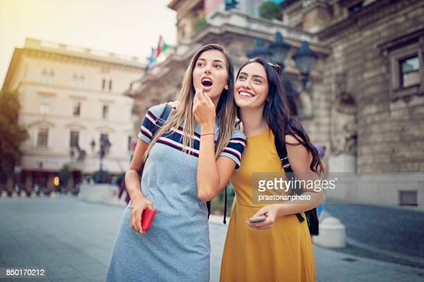 Young, happy girls are standing awe at the front of  famous place