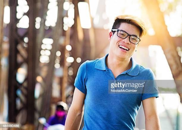 young happy handsome vietnamese man smiling long bien bridge hanoi - vietnamese culture stock pictures, royalty-free photos & images