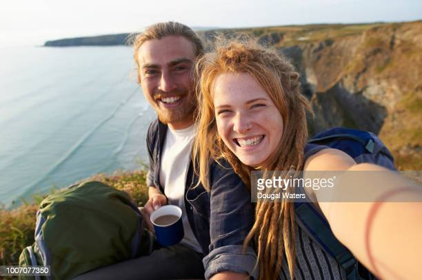 young happy hiking couple taking self portrait on an atlantic coastline. - dougal waters stock pictures, royalty-free photos & images