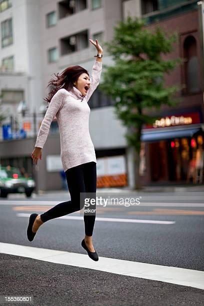 Young happy Japanese woman jumping to catch taxi in Tokyo
