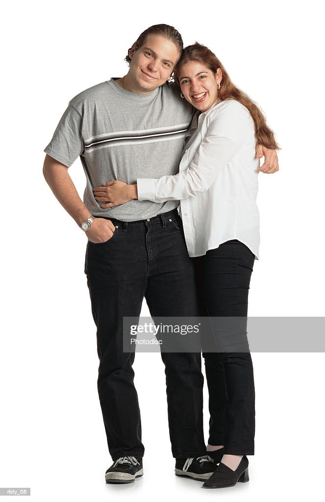 young happy latino couple smiles while holding each other lovingly and looking into the camera : Foto de stock