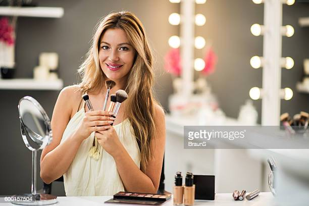 Young happy make-up artist with brushes in beauty salon.