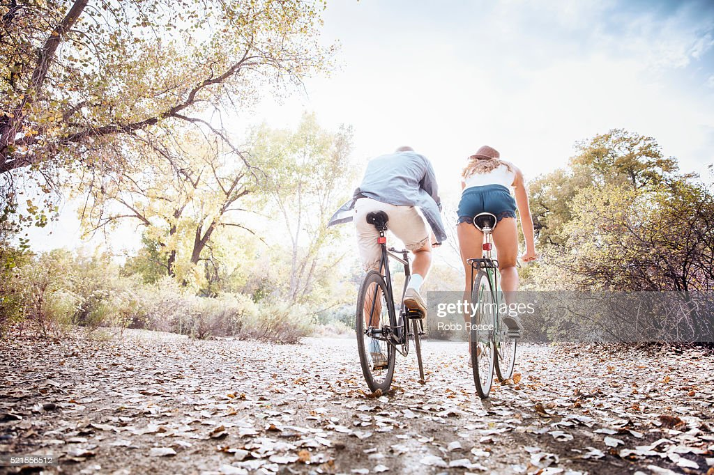 A young, happy man and woman riding bicycles in a city park for fitness : Stock Photo