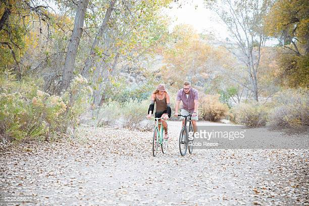 a young, happy man and woman riding bicycles in a park for fitness - robb reece stock pictures, royalty-free photos & images