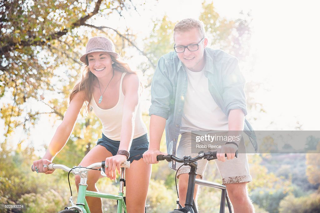 A young, happy man and woman riding bicycles in a park for fitness : Stock Photo