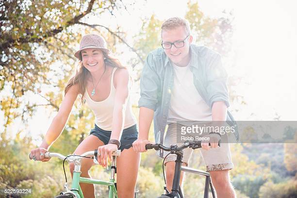 a young, happy man and woman riding bicycles in a park for fitness - robb reece stock photos and pictures