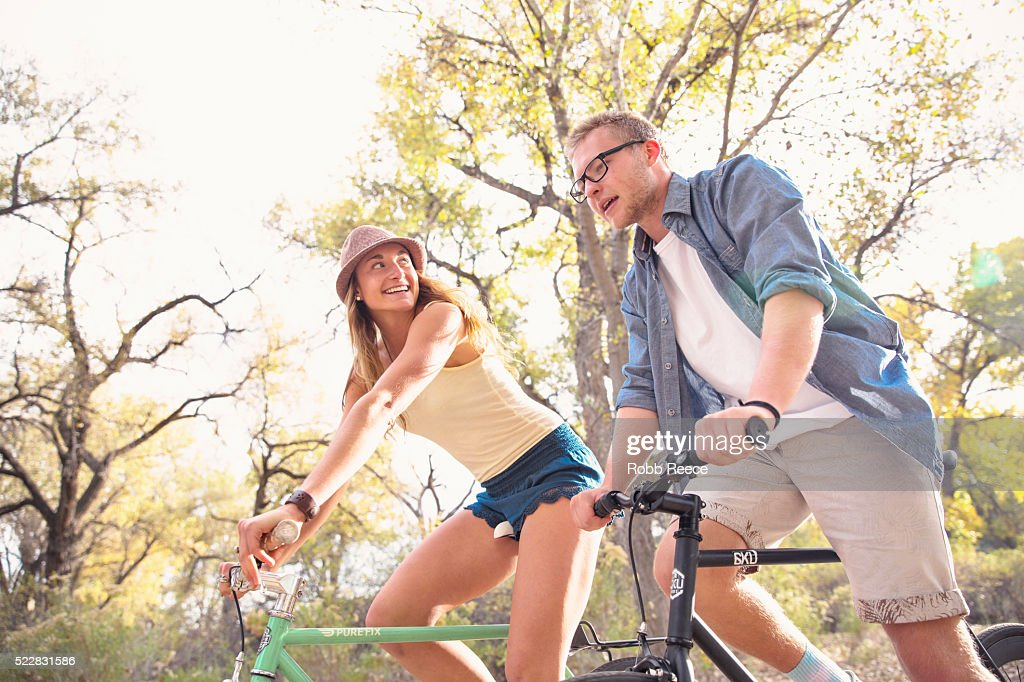 A young, happy man and woman riding bicycles in a park for fitness : Stockfoto