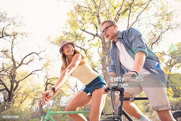 a young, happy man and woman riding bicycles in a park for fitness - robb reece stockfoto's en -beelden