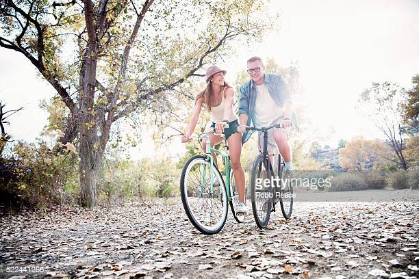 a young, happy man and woman riding their bicycles in a park - robb reece stock-fotos und bilder