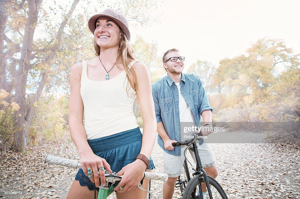 A young, happy man and woman standing with their bicycles in a park : Stock Photo