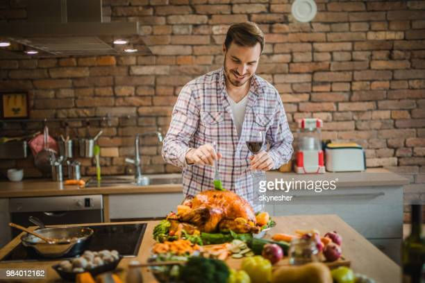 young happy man basting roasted thanksgiving turkey in the kitchen. - basting brush stock photos and pictures