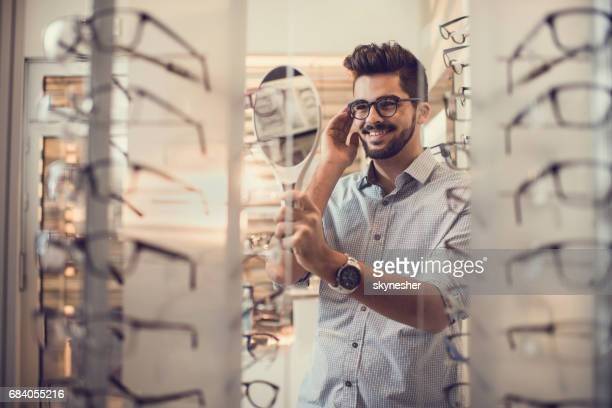 gelukkig jongeman kiezen van brillen bij opticien store. - brillen en lenzen stockfoto's en -beelden