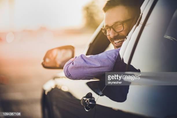 young happy man driving a car at sunset. - conduzir imagens e fotografias de stock