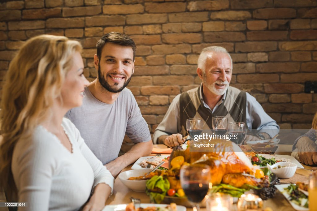 Young happy man enjoying in Thanksgiving dinner with family. : Stock Photo