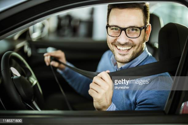 young happy man fastening his seatbelt before a trip by car. - fastening stock pictures, royalty-free photos & images
