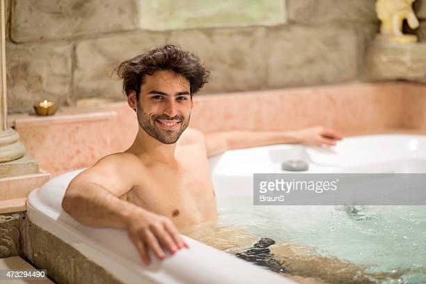 Young happy man tener una hidroterapia en el jacuzzi.