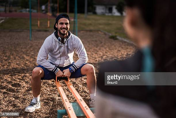 Young happy man having fun with his girlfriend on seesaw.