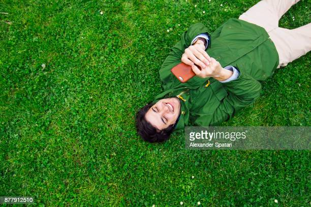 young happy man lying on the grass and using smart phone - verde descrição de cor - fotografias e filmes do acervo
