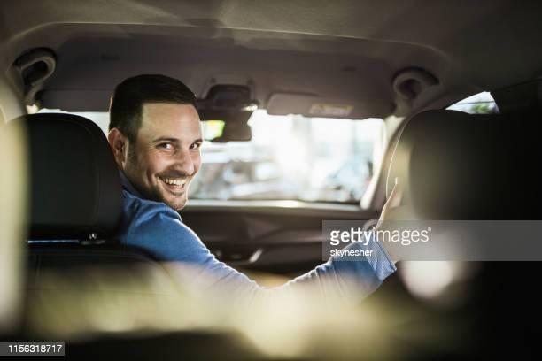 joven hombre feliz aparcando su coche en marcha atrás. - aparcar fotografías e imágenes de stock