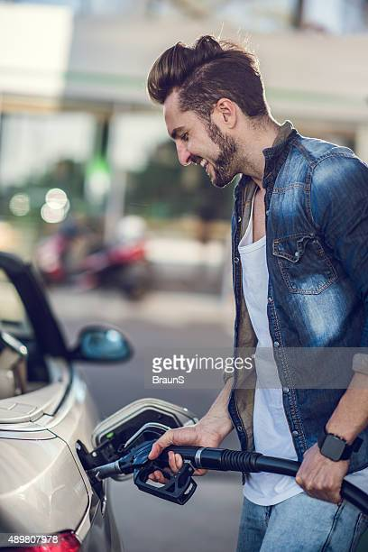Young happy man pumping gas at gas station.