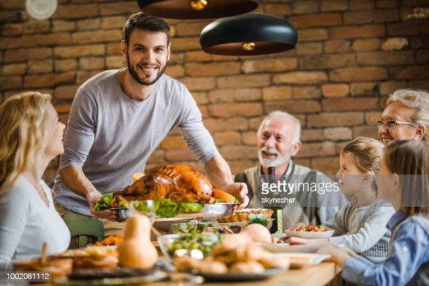Young happy man serving his family stuffed turkey on Thanksgiving dinner at dining table.