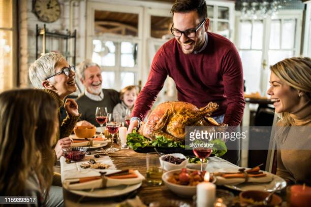 young happy man serving thanksgiving turkey for his family at dining table. - thanksgiving stock pictures, royalty-free photos & images