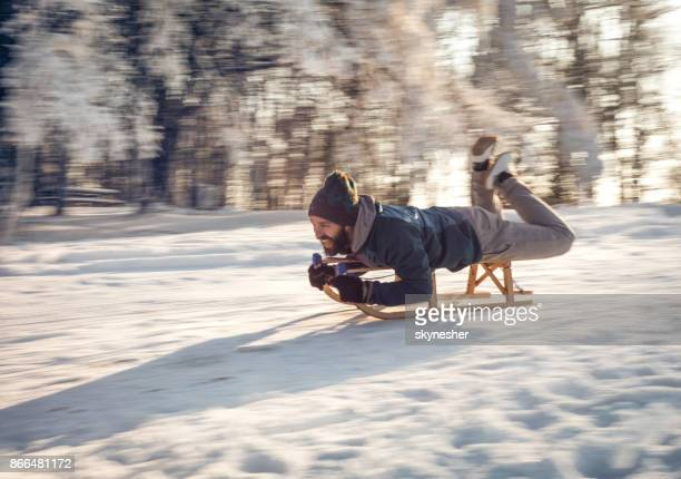 Young happy man sledging on a snow in blurred motion.