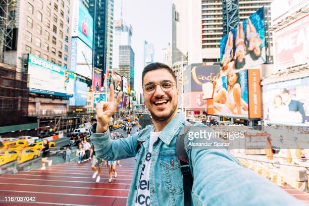 young happy man taking selfie and showing peace gesture at times square, new york city, usa - selfie stock pictures, royalty-free photos & images