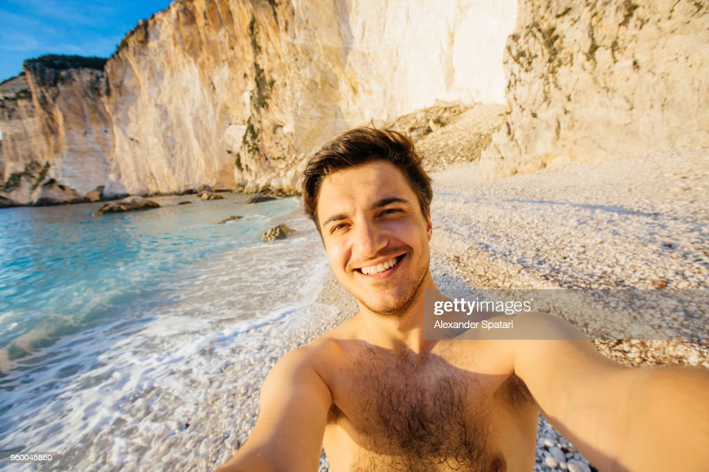 Young happy man taking selfie on the beach in Greece : Stock-Foto
