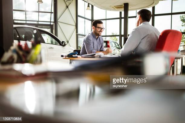 young happy man talking to car salesperson in a showroom. - showroom stock pictures, royalty-free photos & images