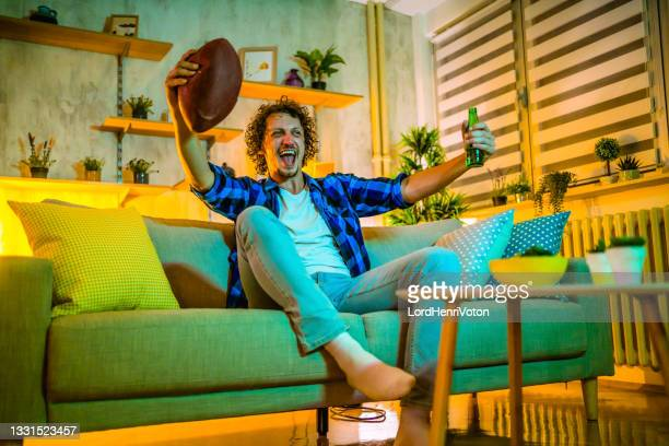 young happy man watching american football on tv - football league stock pictures, royalty-free photos & images