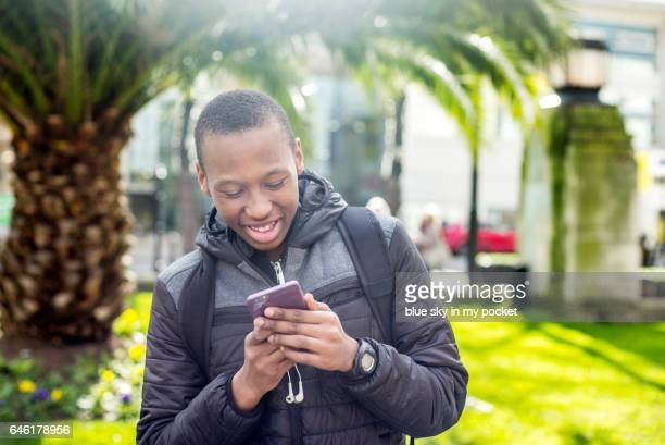 a young happy man with his smart phone. - one young man only stock pictures, royalty-free photos & images
