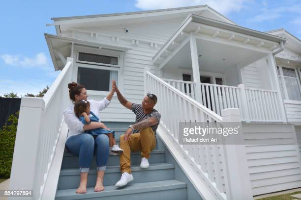 Young happy Maori family sit on their new home stairs