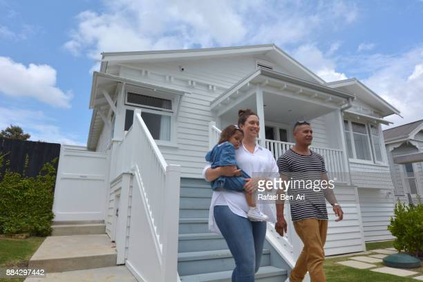 Young happy Maori family walk out of their new home
