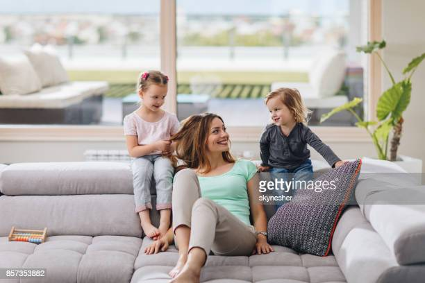 young happy mother enjoying with her kids on the sofa in the living room. - penthouse girl stock photos and pictures