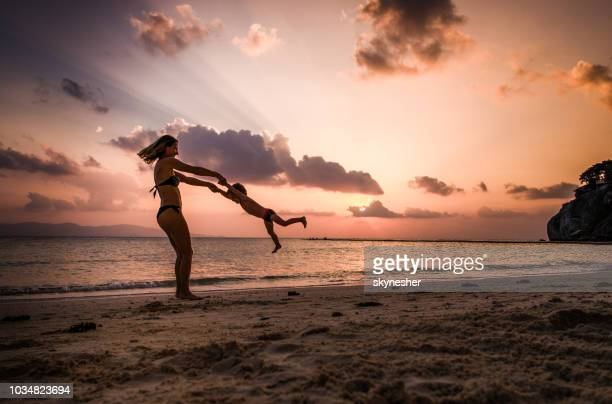 young happy mother having fun while spinning her son on a beach at sunset. - surat thani province stock pictures, royalty-free photos & images