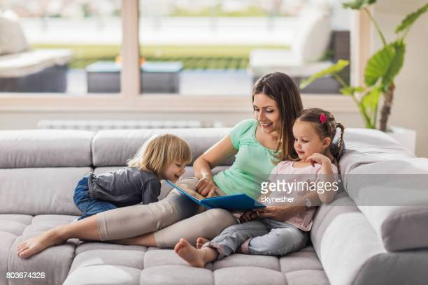 young happy mother reading a story to her children at home. - penthouse girls stock pictures, royalty-free photos & images