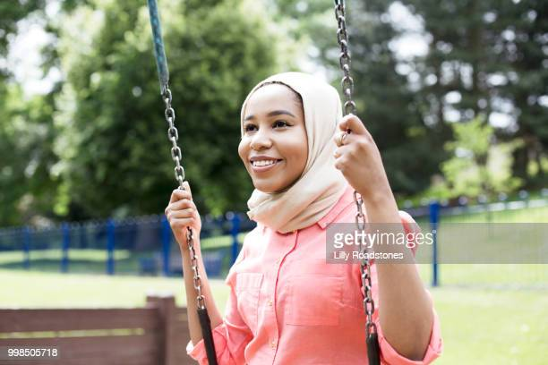 Young happy muslim woman on swing in public park