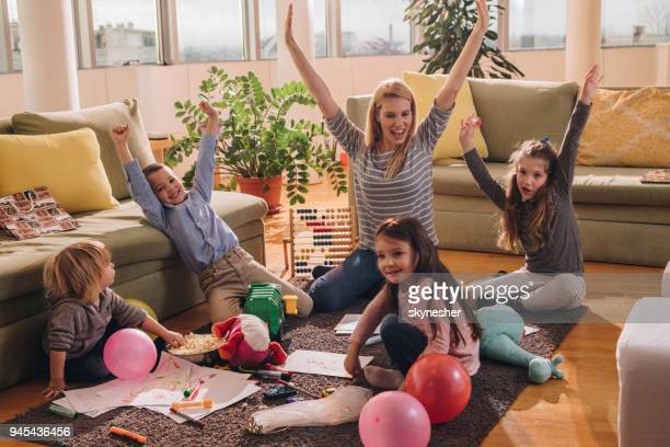 young happy nanny having fun with small kids in the living room. - nanny stock photos and pictures