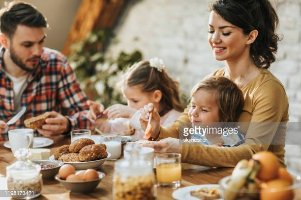junge glückliche eltern genießen mit ihren kindern während des frühstücks am esstisch. - frühstück stock-fotos und bilder