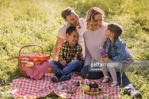 Young happy parents enjoying with their kids during picnic day in springtime.