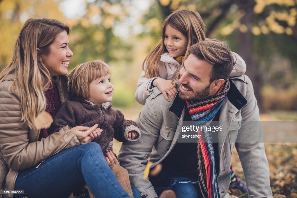 Jonge gelukkige ouders genieten met hun kleine kinderen in herfstdag. : Stockfoto