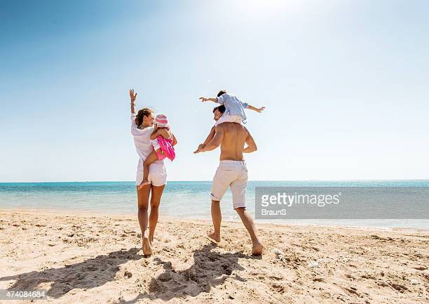 young happy parents having fun with their children at beach. - family with two children stock pictures, royalty-free photos & images