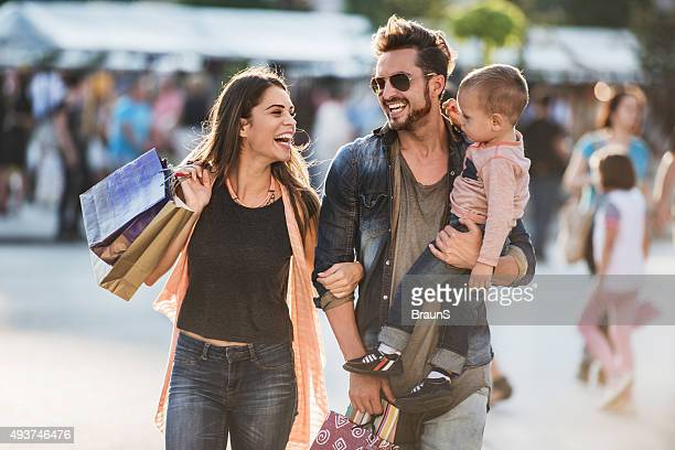 young happy parents having fun with their son in shopping. - winkelen stockfoto's en -beelden
