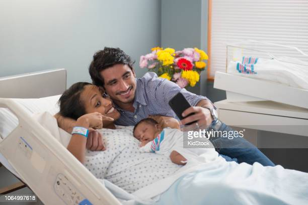 Young happy parents taking a selfie with their newborn baby at hospital