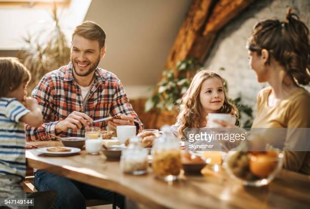 jovens pais felizes falando com seus filhos durante a hora do almoço, na mesa de jantar. - mesa de jantar - fotografias e filmes do acervo