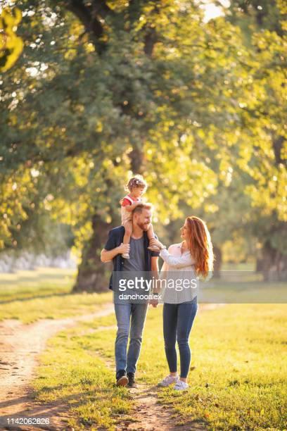 jonge gelukkige ouders met hun baby meisje plezier buitenshuis - familie met één kind stockfoto's en -beelden