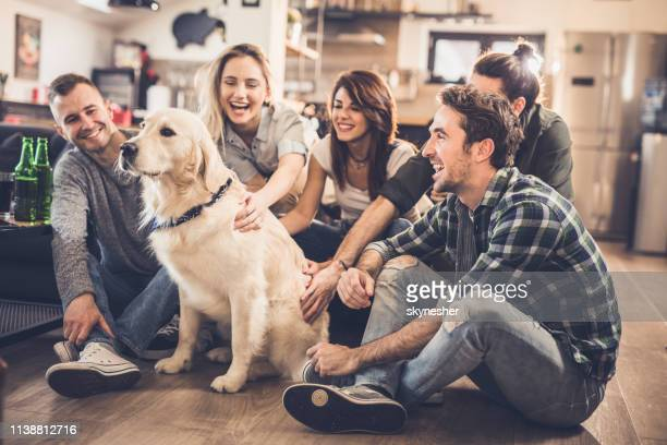 Young happy people enjoying with their golden retriever at home.