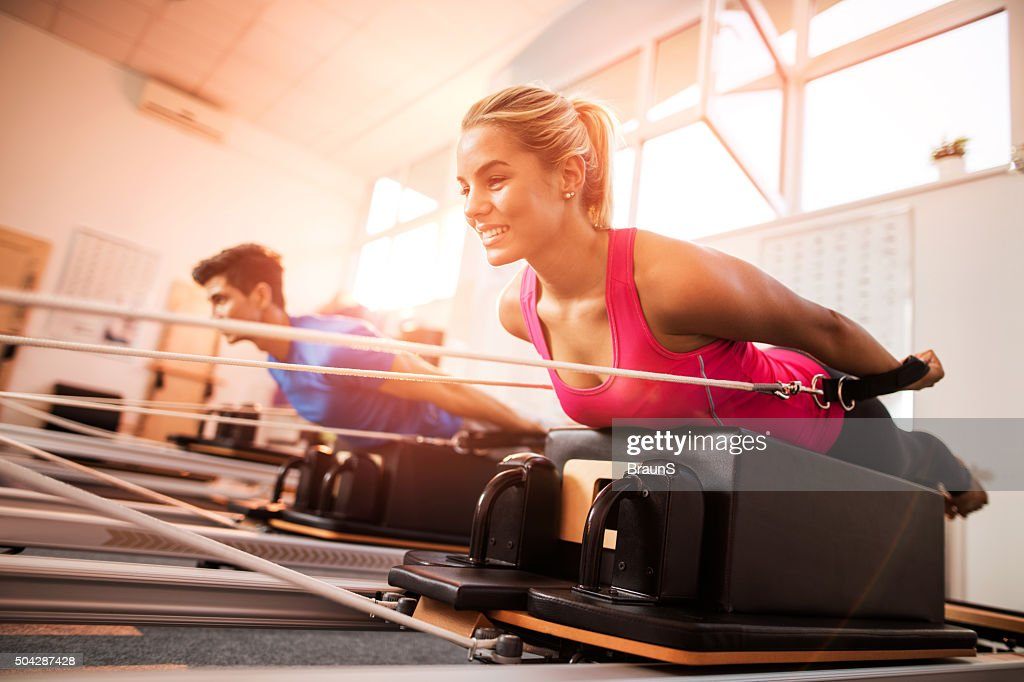 Young happy people exercising on Pilates machines at health club. : Stock Photo