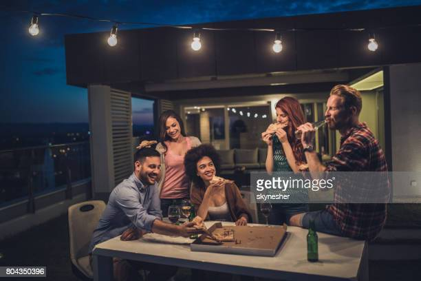 Young happy people having a dinner party during the night on a terrace.
